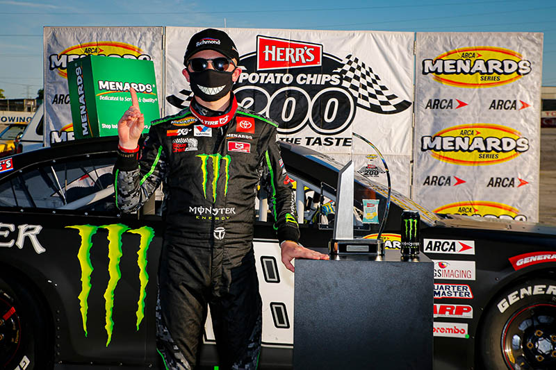 Ty Gibbs Herr's Potato Chips 200 victory photo with his race car behind him.
