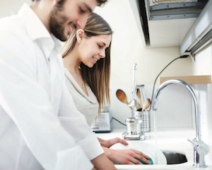 Couple washing dishes at house sink