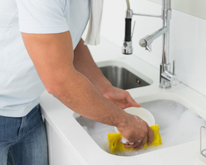 Man washing dishes in house sink