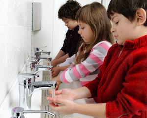 Children washing hands at communal sink